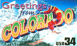 Colorado Greeting: A male skier in red plunges down a snowy slope on the right, against a backdrop of two mountains in Aspen, a popular Colorado ski resort.