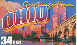 Ohio Greeting: depicts the skyline of Cleveland, including the well-known Terminal Tower, with the city's Veterans Memorial Bridge over the Cuyahoga River in the foreground. The sun hangs low in the sky behind the buildings, casting a pink glow on billowing cumulus clouds at the side.